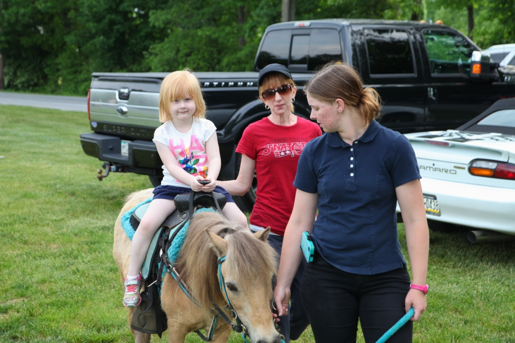 Enjoying a pony ride before the show.  Pictured: Olivia Beck (great-granddaughter of founders William and Alice Beck), alongside her mother Mindy Mertz-Beck.